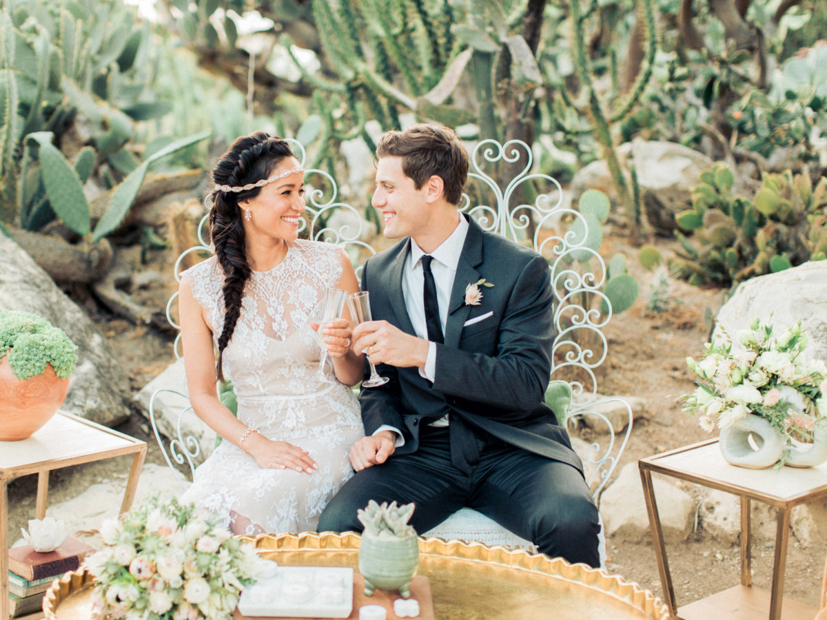 Newlyweds toast in a desert oasis accented by wedding florals by La Petite Gardenia.