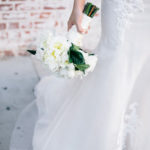 Waist down shot of bride holding a white bridal bouquet.