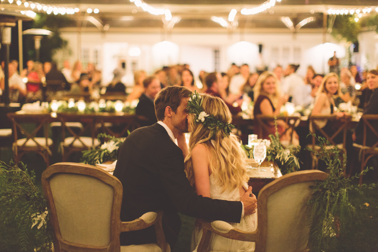 Photo of Tyler Hilton and Megan Park kissing at their wedding table.