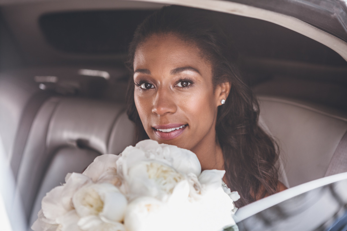 A close up of a bride with her bridal bouquet through a car window.