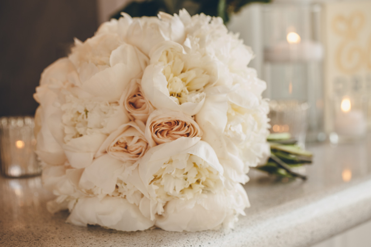 A blush bridal bouquet lies on a table