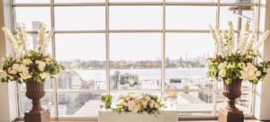 Two large floral arrangements frame a floral wedding centerpiece in front of a wall of windows.