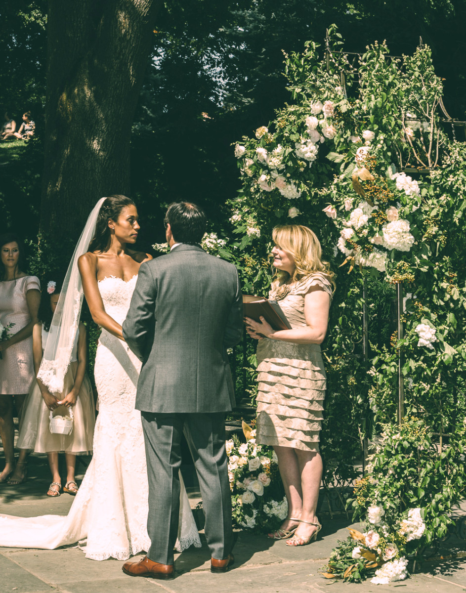 A couple is married in the park in front of a floral archway.