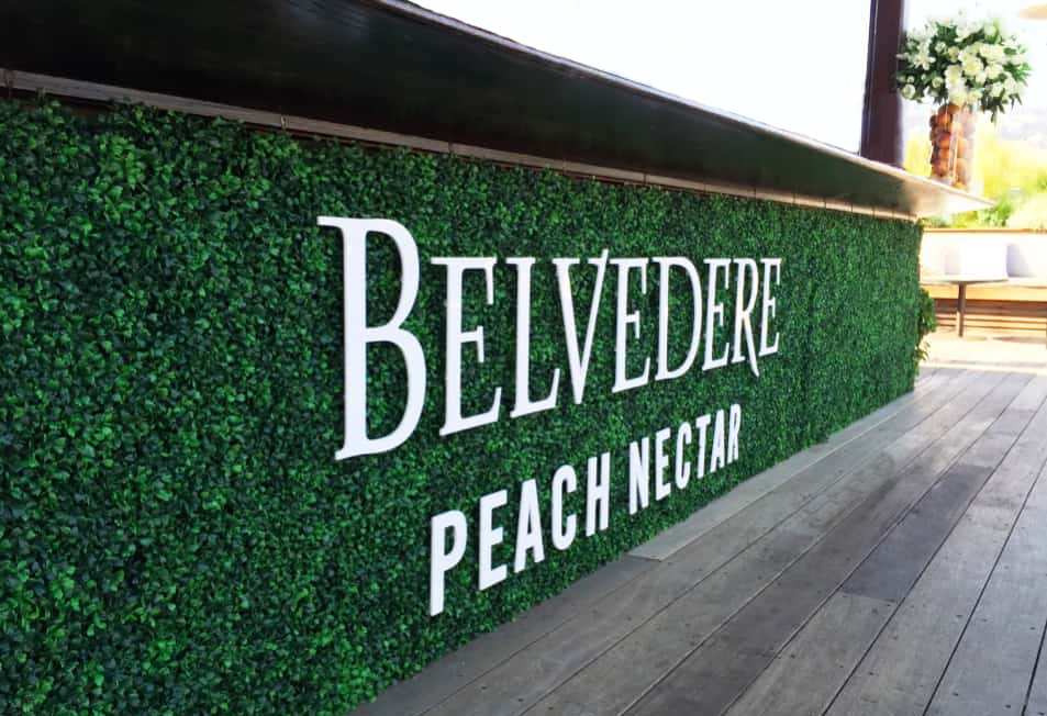 "A floral wall beneath the bar with green leaves and lettering that reads ""Belvedere Peach Nectar""."