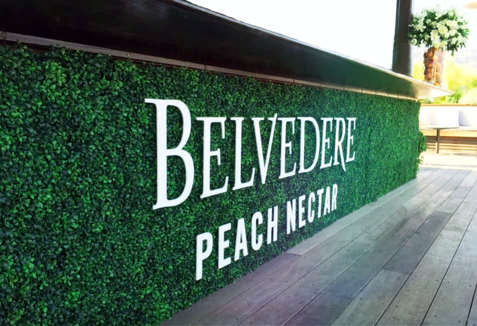 """A floral wall beneath the bar with green leaves and lettering that reads """"Belvedere Peach Nectar""""."""