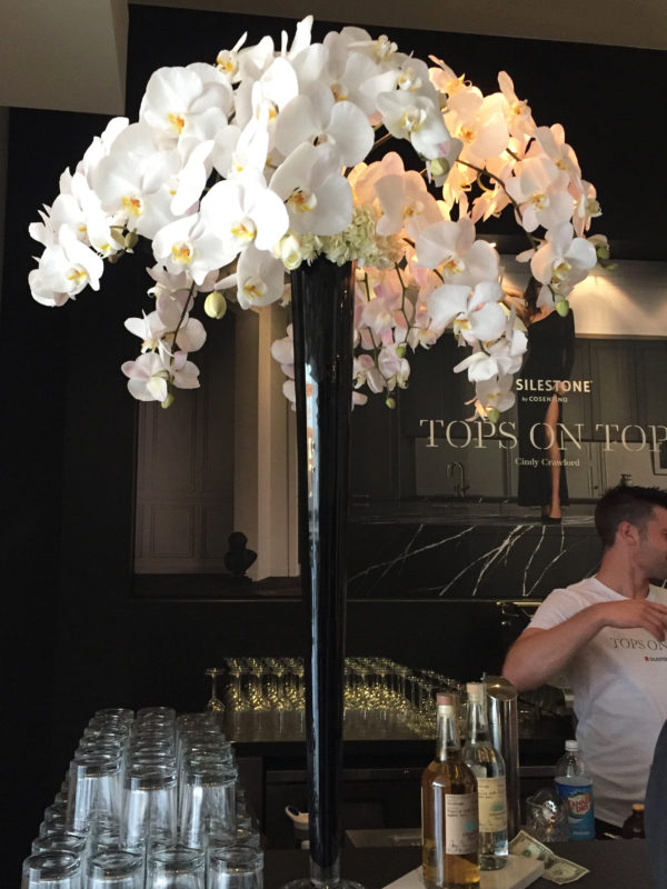 A tall white orchid arrangement in a black vase sits atop a bar at a Cindy Crawford & Silestone® event in Hollywood, CA.