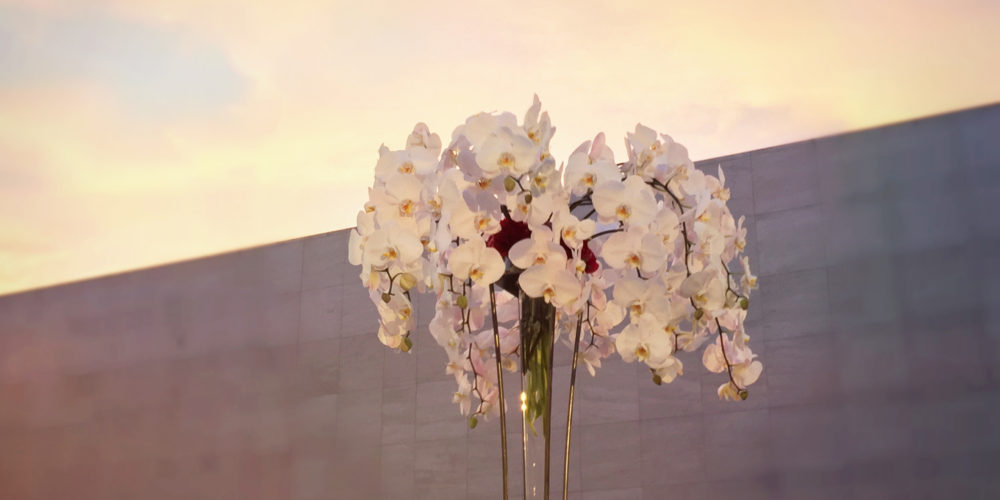 A huge white orchid arrangement in a tall glass vase is framed by the sunset at a corporate event.