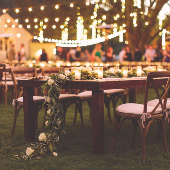 Photo of romantic family style wedding place settings with white rose centerpieces.