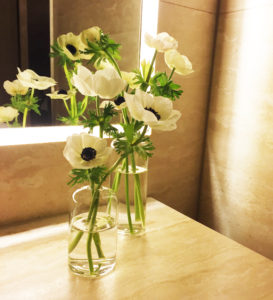 White anemones rest in glass bud vases on a bathroom table at a Hollywood event.